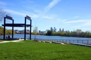 Green space overlooking river with Center City skyline view